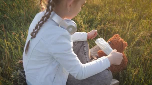 Trauriges kleines Mädchen und Teddybär mit Chirurgenmaske bei Sonnenuntergang. Ein Kind hält seinen Teddybär während der Quarantäne. Covid-19-Pandemie-Coronavirus.