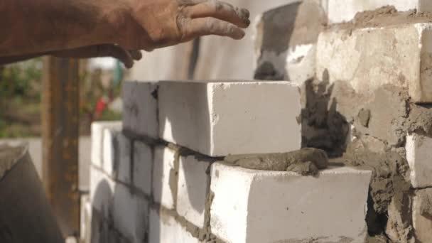 Stavební dělník nebo zedník pokládající cihly a vytvářející zdi. Zedník pokládající cihly, aby udělal zeď. Stavba betonové zdi pro dům.