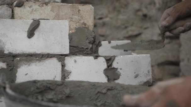 Construction worker or mason laying bricks and creating walls. Bricklayer laying bricks to make a wall. Building a cement block wall for a house.