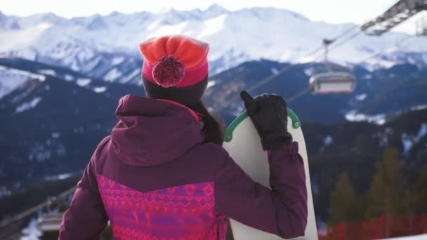 Snowboarderin mit Snowboard auf Berggipfel im Skigebiet. Wintersport und Winterurlaubskonzept. Sonniger Wintertag im Skigebiet.