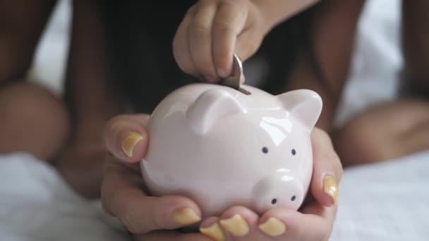 A család érméket tesz a malacperselybe a jövőbeli megtakarítások érdekében..