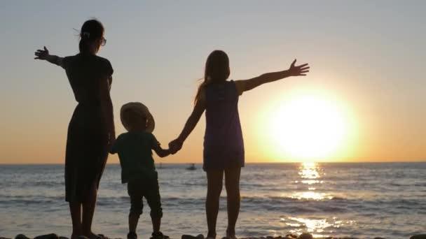 Šťastná rodina Matka s dvěma dětmi na dovolené na pláži. Silueta matka se dvěma dětmi v moři při západu slunce.