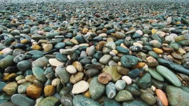 Pohled zepředu na mořské vlny narážející na skály. Skála s velkými kameny v moři a vlny s pěnou.