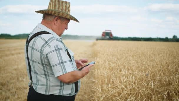 Agronomický mladík používající smartphone na zemědělské farmě. Farmář s mobilním telefonem v pšeničném poli na pozadí pracovního kombajnu.