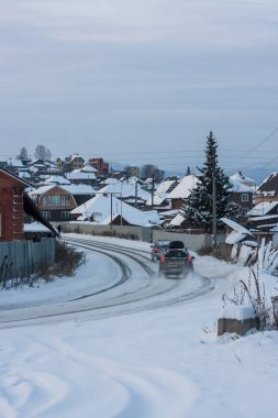 the car is entering a dangerous turn on a slippery winter road. ice and snow is extreme road surface. SUV on winter tires