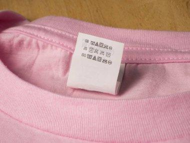 Clothing label washing instruction tag on pink t-shirt