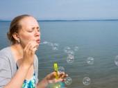 Zblízka pohled uvidí mladých žen modelu foukání mýdlové bubliny na krásné moře a pláž zázemí.