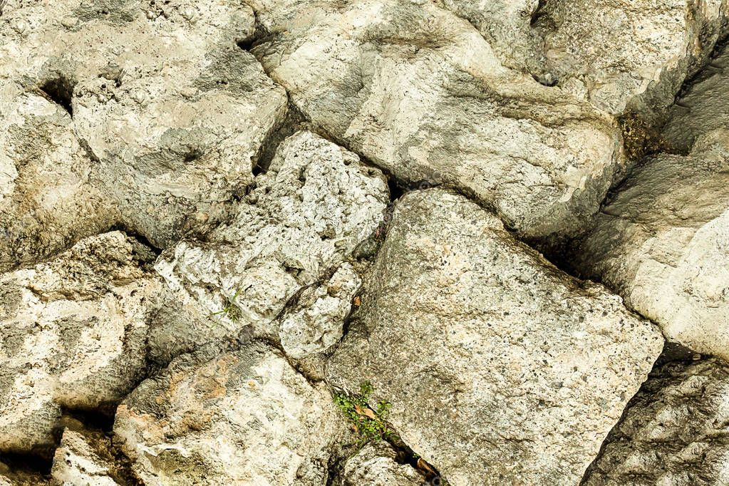 pile of stones gray beige part of the hill rock weathered uneven old surface
