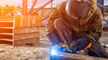 A young  man welder in brown uniform, welding mask and welders leathers, weld  metal  with a arc welding machine at the construction site, blue sparks fly to the sides stock vector