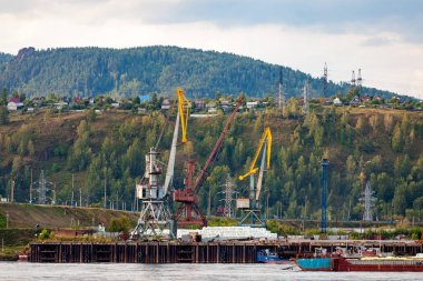 Landscape of a  huge industrial construction: several working cranes on the river, barges with cargo and on a background of a  industrial city with small houses