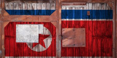 Close-up of old warehouse gate with national flag of North Korea. The concept of export-import North Korea, storage of goods and national delivery of goods. Flag in grunge style