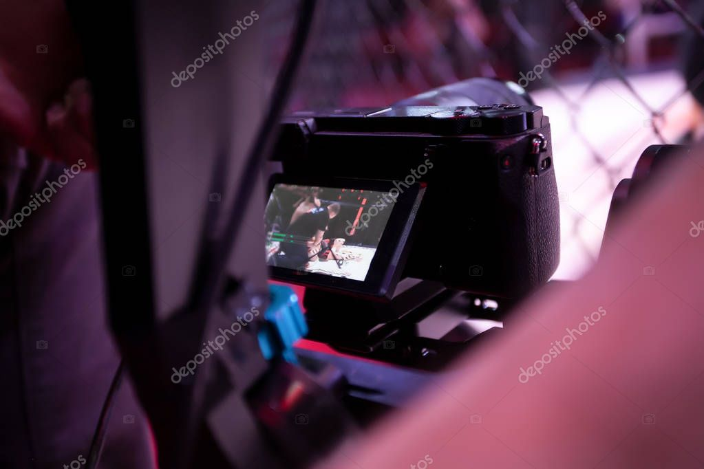 Video filming in the backstage of a sporting event. Athletes fighters in oktogon in front of the camera after the fight. Operator with a professional video camera during the event, rear view stock vector
