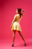 Young seductive woman in a yellow dress in the style of a new look swirls, poses and has fun on a pink isolated background. The concept of female beauty and grace, posing in a photo studio
