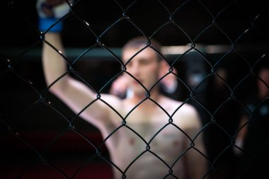 Close-up of the metal cage,in the background arena of the octagonal scene by the a young fighter holds his fist up as a sign of victory, in the background is the judge. Fights without rules according to MMA version