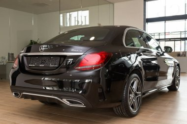 Novosibirsk/ Russia  April 28, 2020:  black Mercedes-Benz C-class,   back view.  New expensive sedan made in  Germany in autosalon stock vector