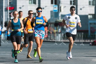 Novosibirsk, Russia - September 12, 2020: Raevich Half Marathon. Athletes run in jogging along the street on a summer day