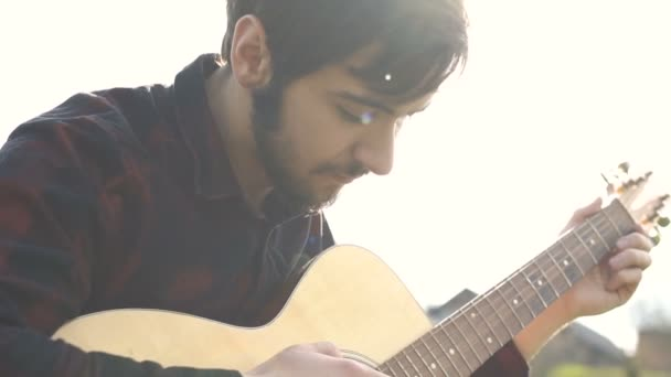 Man playing on a guitar outdoors. Playing music on a acoustic guitar.