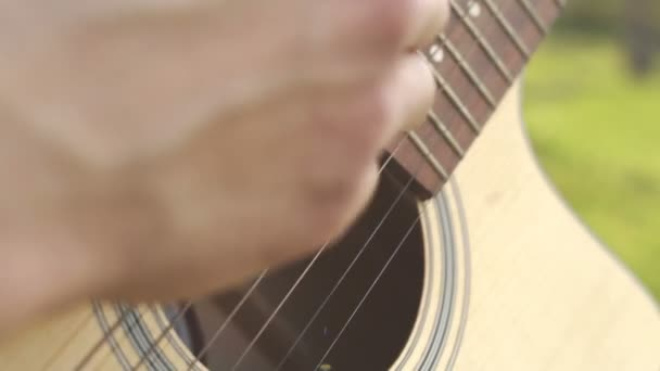 Man playing on a guitar outdoors. Playing on a acoustic guitar. Hand on strings