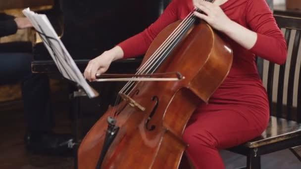 Violoncellové hráč. Violoncellista ruce hraje violoncello s mašlí.