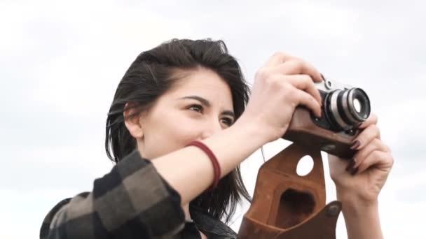 Mädchen beim Fotografieren, im Hemd, das mit einer alten analogen Kamera fotografiert