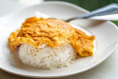 Easy Thai food menu, Thai omelette over rice or Kai Jeaw Rad Kow. Close up Thai omelette over white rice in white plate on table.