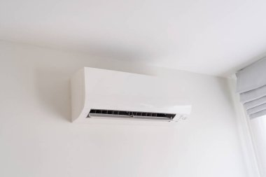 Air conditioner on white concrete wall in area of bedroom space.