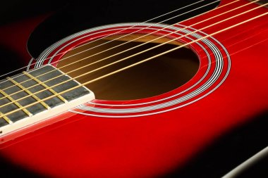 Closeup of a six stringed red acoustic guitar. Music entertainment background.
