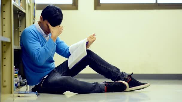 Mladý student Studuj v knihovně. Asijské muži univerzitní student dělá studie výzkum v knihovně knihu na podlaze a zaměření. Pro zpátky do školy rozmanitost koncepce