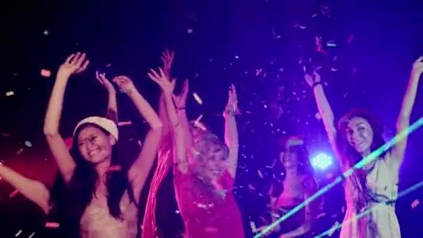 Sok nő, tánc, ujjongott party zene meg a táncparketten, egy éjszakai klub, a csökkenő konfetti jóképű férfi többnemzetiségű csoportja. Közepes lövés, lassú mozgás.