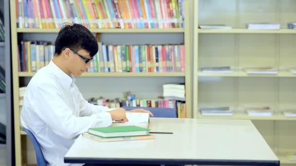 Mladý student Studuj v knihovně. Asijské muži univerzitní student dělá výzkum studijní knihovna s knihami o stůl a usmívá se. Pro zpátky do školy rozmanitost koncepce