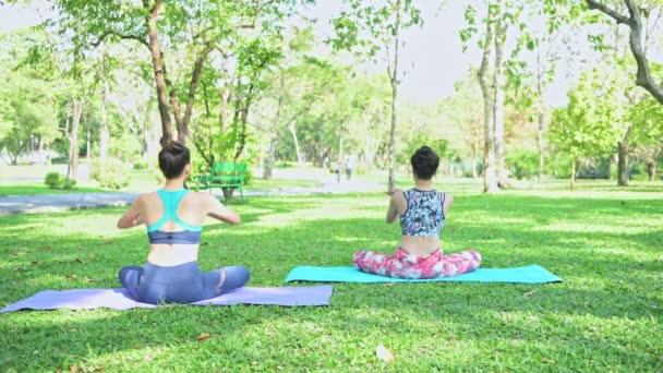 Žena učí jóju v parku. Cvičení jóby a relaxace ve veřejném parku.