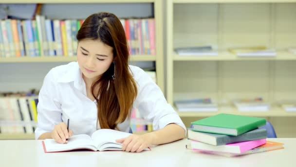Mladý student Studuj v knihovně. Asijské žena univerzitní student dělá výzkum studijní knihovna s knihami o stůl a usmívá se. Pro zpátky do školy rozmanitost koncepce