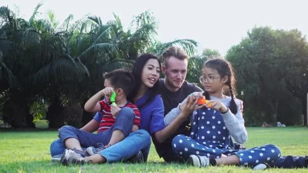 Rodinná bublina v parku. Smíšená rasa s bílým mužem, čínskou ženou a jejich dětmi. Sedět pohromadě na trávě v parku a bavit se spolu.