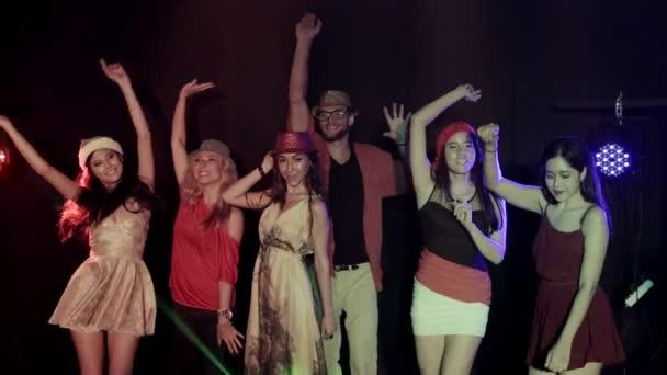 multi-ethnische Gruppe von gut aussehenden Mann mit vielen Frauen tanzen, jubelnde Party-Musik mit Freunden auf der Tanzfläche eines Nachtclubs. Mittlerer Schuss, Zeitlupe.