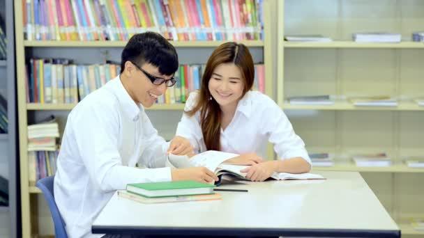 Mladí studenti se pilně studovat v knihovně. Happy asijské ženské a mužské vysokoškolských studentů dělá studie výzkum v knihovně knihy na stole, poznámkového bloku. Pro zpátky do školy rozmanitost koncepce