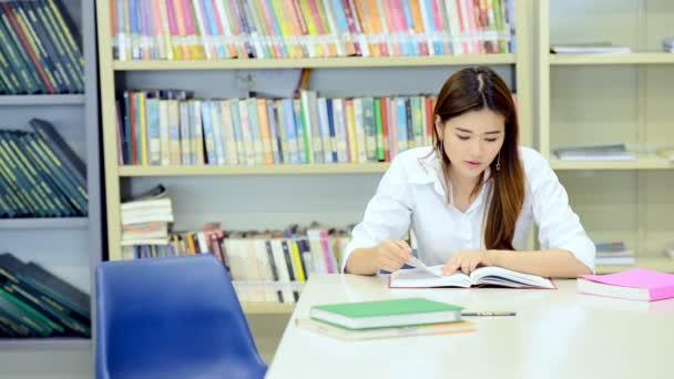 Fiatal diák tanulmányi kemény könyvtárban. Ázsiai nő egyetemi hallgató tanulmányi könyvtár könyveket a pultnál, és mosolyogva kutatás során. A vissza az iskolai oktatás sokszínűség koncepció.