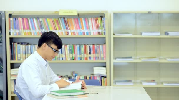 Young student study hard in library. Asian male university student doing study research in library with books on desk and smiling. For back to school education diversity concept.