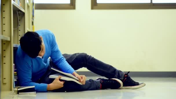 Mladý student Studuj v knihovně. Unavený asijské mužské univerzitní student dělá studie výzkum v knihovně knihu na podlaze a na podzim do režimu spánku. Pro zpátky do školy rozmanitost koncepce