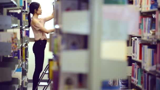 Asijské univerzity pojetí života. Mladý dospívající studentka v univerzitní knihovně hledají knih pro její studium. Asijská dívka šaty v červené tričko a džíny.