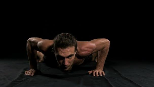 Muž dělá push up s černým pozadím. Napůl nahý muž, pomalý pohyb.