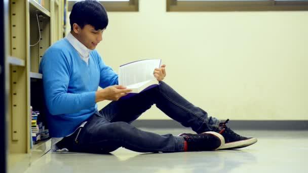 Fiatal diák tanulmányi kemény könyvtárban. Ázsiai férfi egyetemi hallgató könyvtár olvasás könyv a padló és a fókuszáló tanulmány kutatás során. A vissza az iskolai oktatás sokszínűség koncepció.