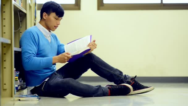 Young student study hard in library. Asian male university student doing study research in library reading book on floor and focusing. For back to school education diversity concept.