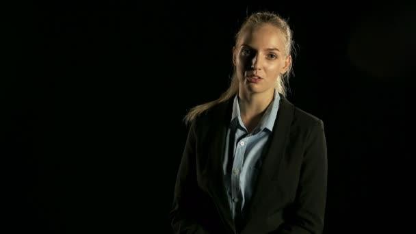 Mladá krásná žena v šatech mluvit před kamerou v černém pozadí bílé