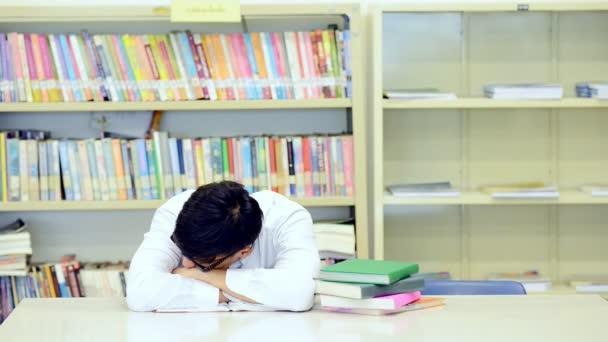 Mladý student Studuj v knihovně. Unavený asijské mužské univerzitní student dělá výzkum studijní knihovna s knihami o stůl a pocit únavy. Pro zpátky do školy rozmanitost koncepce