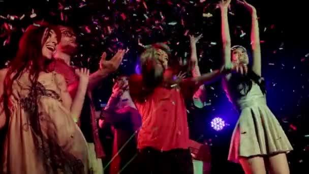 Gruppo multi-etnico delluomo bello con molte donne ballare, musica di festa con gli amici sulla pista da ballo di un night club con i coriandoli che cadono il tifo. Mezzo colpo, rallentatore.