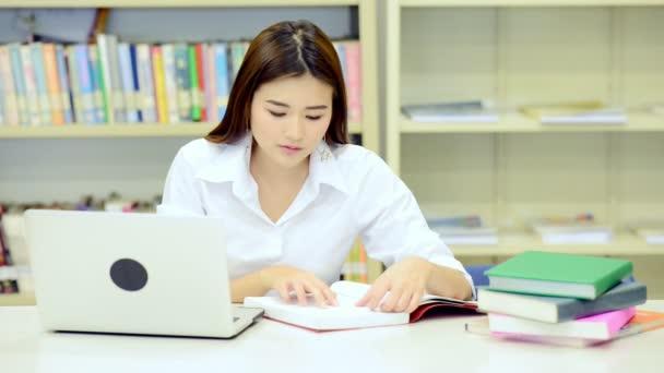 Mladý student Studuj v knihovně. Happy asijské ženské univerzitní student dělá studie výzkum v knihovně knihy na stole, poznámkového bloku. Pro zpátky do školy vzdělávací technologie koncept.