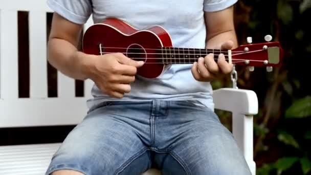 Young man in short blue jeans and blue tshirt playing small travel guitar on white bench outdoor on sunny day. For vacation, travel and music relaxation concepts.