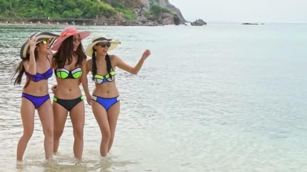 schöne chinesische Frauen am Strand. Gruppe attraktiver junger chinesischer Frauen, die sich am Strand vergnügen. Wasser laufen und treten. Schuss in Zeitlupe. Filmlook. pattaya, thailand.