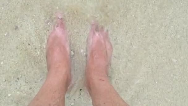 Male feet on the beach at seaside. Point of view look down angle. Man with bare foot standing on the seashore with water covering the feet. Summer and relax concepts. Slow motion.