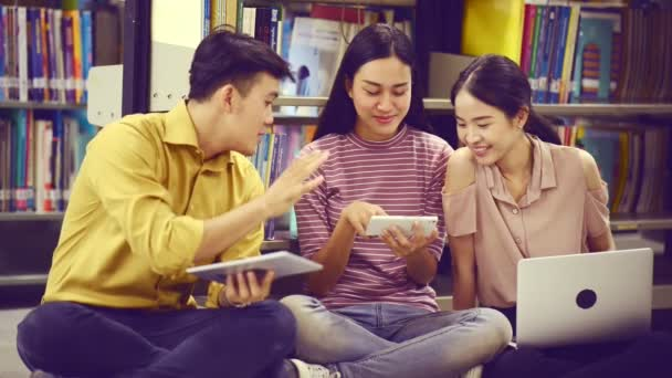 Asian university life concept. Attractive asian female student doing research in library with her male student friend taking note in notebook and laptop. With bookshelf as background.